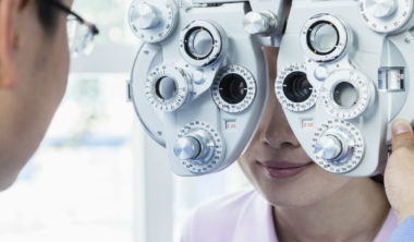 optometrist-doing-an-eye-exam-on-young-woman-PXDLLTQ